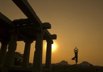 India, Karnataka, Hampi, Silhouette of woman doing yoga near temple at sunset