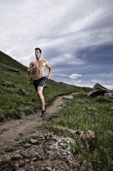 USA, Colorado, Jeferson County, Golden, Shirtless man running long hillside footpath