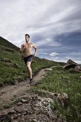 USA, Colorado, Jeferson County, Golden, Shirtless man running long hillside footpath