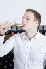 man tasting a glass of white wine.