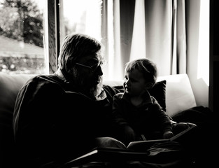Silhouette of grandfather and grandson (18-23 months) reading stories