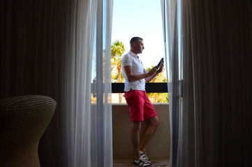 USA, California, Man with digital tablet on balcony