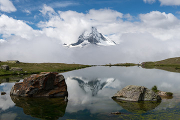 Switzerland, Valais, Zermatt, Rocks in still waters of Stellisee lake and Matterhorn mountain in clouds