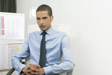 Portrait of businessman contemplating at desk in office