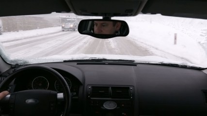 Driver visible in the mirror during the travel in snowy conditions