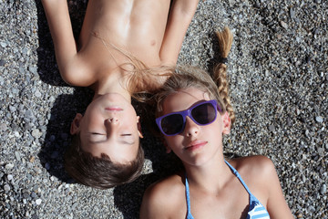 Italy, Children (8-9) sunbathing
