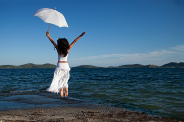 Young woman in white holding umbrella jumping on beach