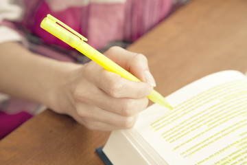 Woman highlighting passage in book, close up