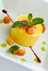Yellow dessert with fruit and mint on white plate