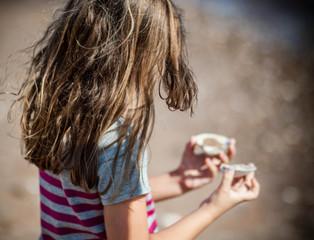 Girl (6-7) holding sea shells on beach