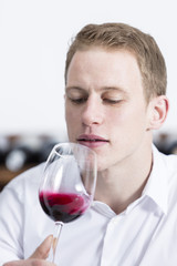 young man shaking a red wine glass.