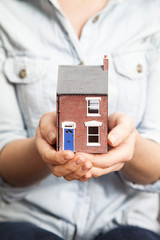 Womans hands holding model house
