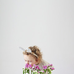 Girl (2-3) wearing bunny ears smelling flowers