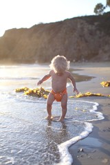 Toddler walking on beach