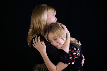 Studio shot of two Sisters (12-13, 16-17) hugging