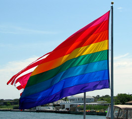 USA, New York, Suffolk County, Fire Island, Rainbow flag flying in front of American Flag