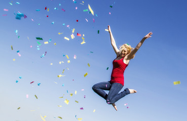 Young woman jumping with confetti