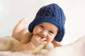 Portrait of baby boy wearing blue knit hat lying on blanket