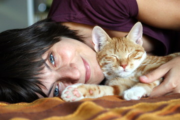 Woman lying on bed with kitten