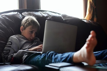 Boy (12-13) using laptop on sofa