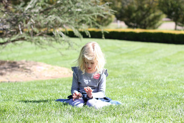 Girl (4-5) sitting on grass