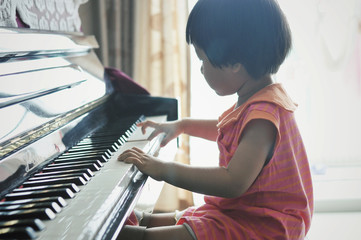 Young girl (2-3) playing piano