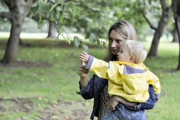 Mother and son looking at leaf