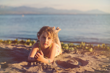 Young girl (4-5) lying on beach