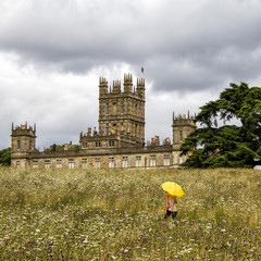 UK, Hampshire, Highclere Castle, Woman with yellow umbrella on meadow