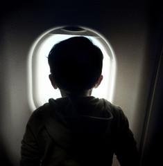Spain, Madrid, Rear view of boy looking through window on airplane