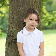 Girl (4-5) standing by tree