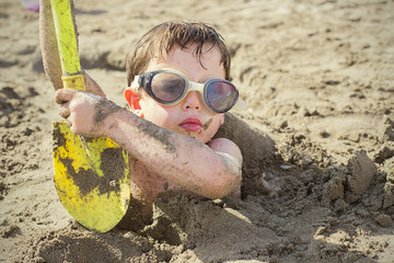 Boy (4-5 years) buried in sand on beach