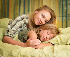 Smiling mother embracing her cute daughter sleeping in bed.