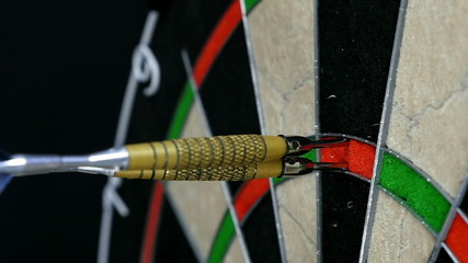 Close up of three darts hitting triple twenty on a dart board