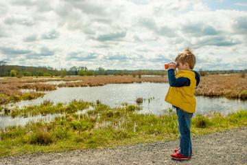Boy looking through binoculars (4-5 years)