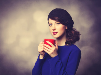 women in blue dress with red cup