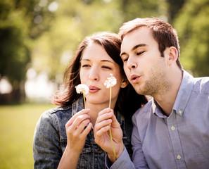 Couple blowing dandelions