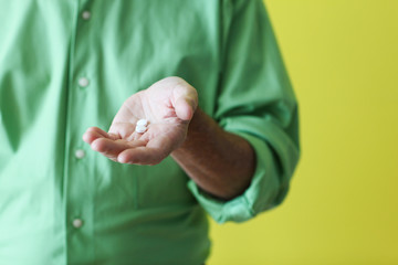 Man holding pills in palm of his hand