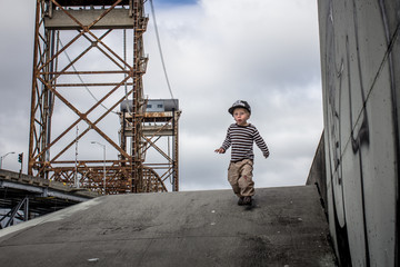 USA, Louisiana, New Orleans, Boy (2-3) running down from levee in Lower ninth ward, Claiborne Bridge in the background