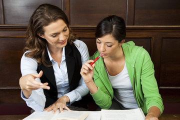 Young woman studying with teacher