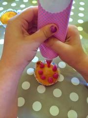 Girl icing a cupcake