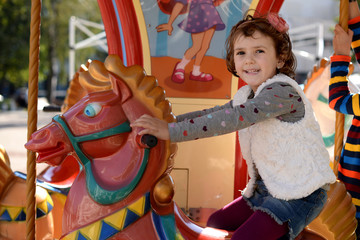 Beautiful little girl (4-5) riding carousel horse