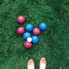 Bocce ball on green grass in park with woman's shoes