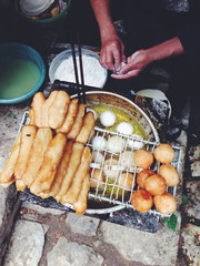 Vietnam, Lao Cai Province, Sa Pa, Woman frying dough on the street