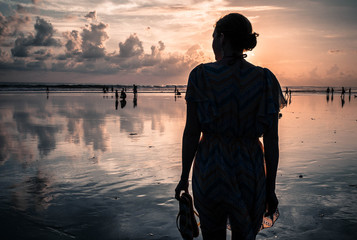 Indonesia, Bali, Legian, Silhouette of woman on beach at sunset