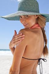 Young woman applying sun cream on beach