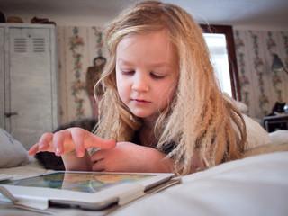 Sweden, Girl (6-7) lying on bed using digital tablet
