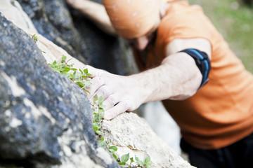 Italy, Man climbing cliff
