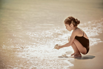 Girl (6-7) crouching by water's edge on sandy beach and holding wet sand in hands