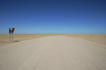 Namibia, View along empty desert road with rest area sign
